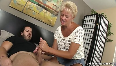 Short-haired mature woman Tracy gives one hell of a handjob
